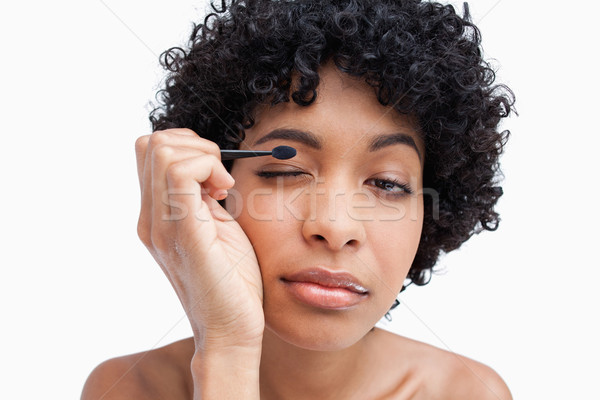 Beautiful young female applying make-up while putting on eye-shadow  Stock photo © wavebreak_media