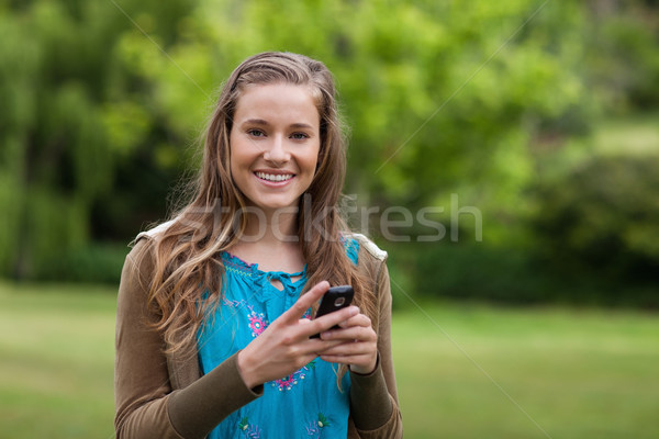 Smiling teenage standing in a park while sending a text with her cellphone Stock photo © wavebreak_media