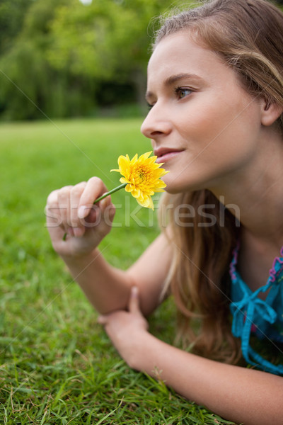 Young relaxed girl lying on the grass in the countryside while smelling a flower Stock photo © wavebreak_media