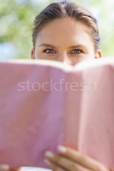 Genç kadın gizleme yüz arkasında kitap park Stok fotoğraf © wavebreak_media