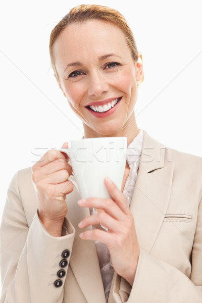 Portrait of a woman in a suit holding a mug against white background Stock photo © wavebreak_media