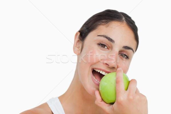 Close-up a brunette eating a green apple against white background Stock photo © wavebreak_media