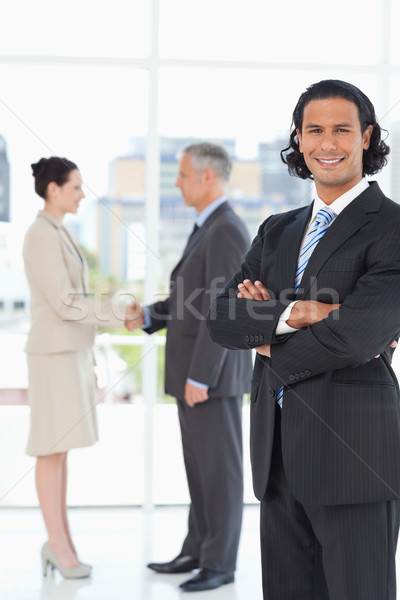 Young executive standing upright in front of business people shaking hands Stock photo © wavebreak_media