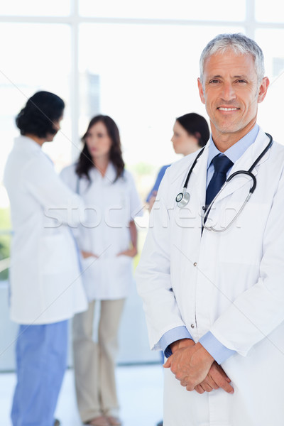 Mature and confident doctor crossing his hands in front of his medical interns Stock photo © wavebreak_media