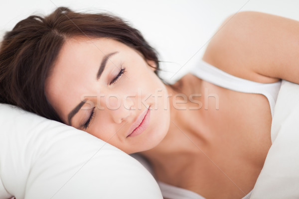 Peaceful brown-haired woman sleeping in the bed in a bright bedroom Stock photo © wavebreak_media