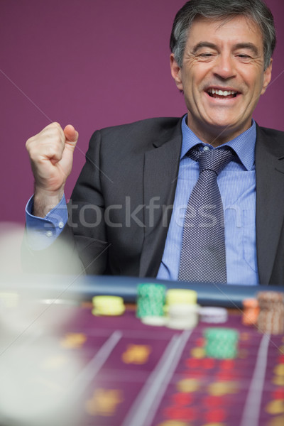 Man sitting at table in a casino and winning in roulette Stock photo © wavebreak_media
