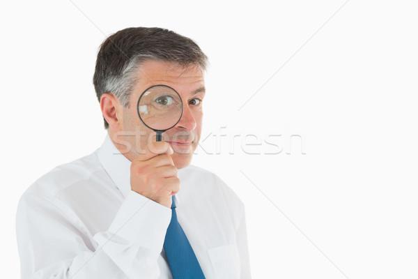 Smiling businessman looking through magnifying glass Stock photo © wavebreak_media