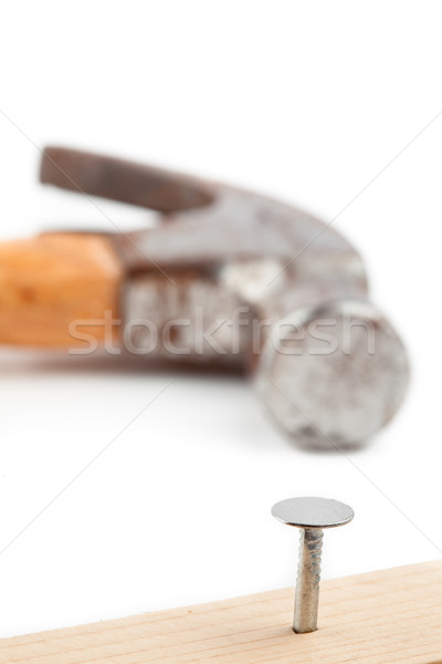 Half nail in a wooden board and the hammer in lying in the backgorund Stock photo © wavebreak_media