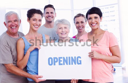 Wellbeing against portrait of happy fit people holding blank boa Stock photo © wavebreak_media