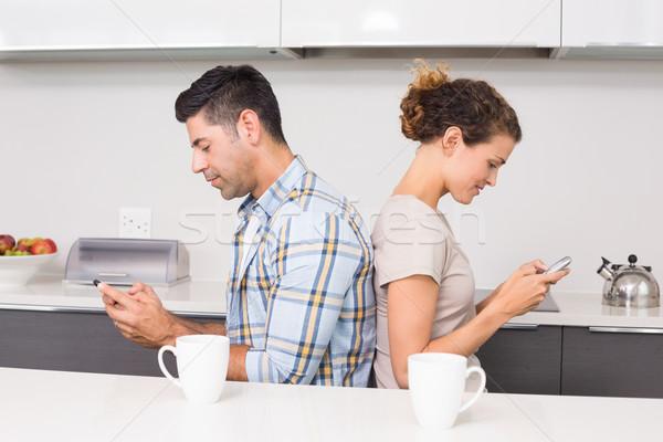 Couple sitting back-to-back texting Stock photo © wavebreak_media