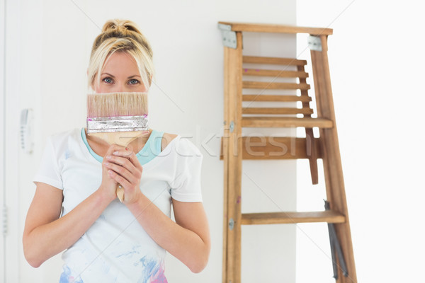 Woman holding paint brush in front of face at new house Stock photo © wavebreak_media