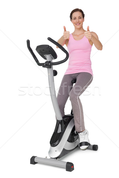 Beautiful woman gesturing thumbs up on stationary bike Stock photo © wavebreak_media
