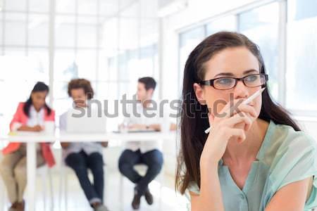 Attractive casual businesswoman holding pencil focusing Stock photo © wavebreak_media