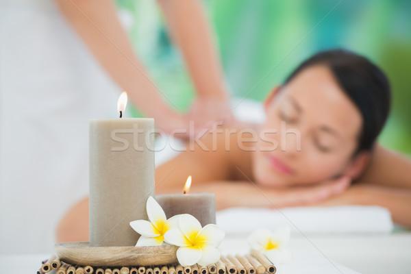 Stock photo: Beautiful brunette enjoying a back massage smiling at camera