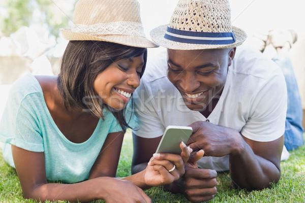 Happy couple lying in garden together looking at smartphone Stock photo © wavebreak_media