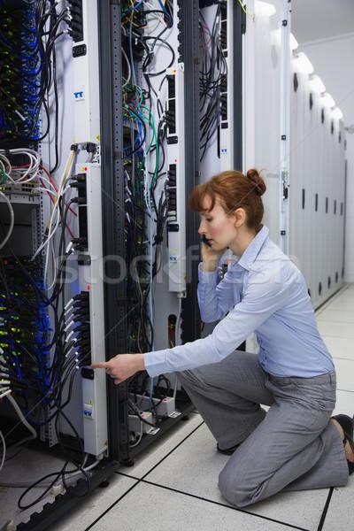 Serious technician talking on phone while analysing server Stock photo © wavebreak_media