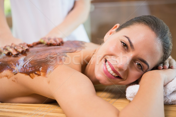 Attractive woman receiving chocolate back mask at spa center Stock photo © wavebreak_media