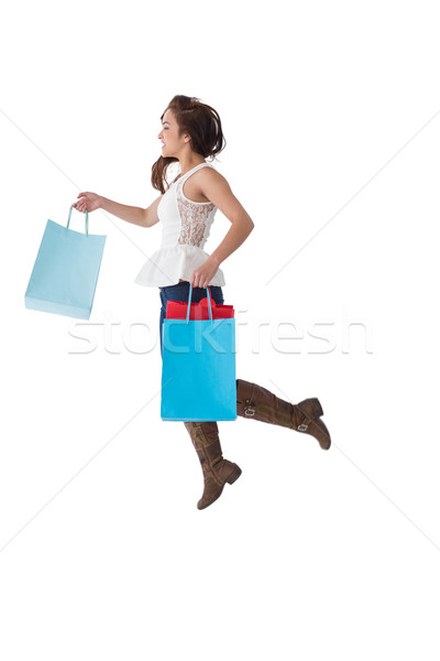 Happy brunette leaping with shopping bags Stock photo © wavebreak_media