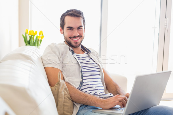 Hipster man using laptop on couch Stock photo © wavebreak_media