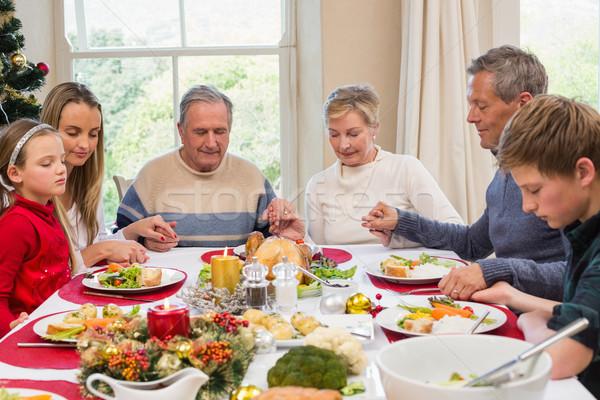 Extended family saying grace before christmas dinner Stock photo © wavebreak_media