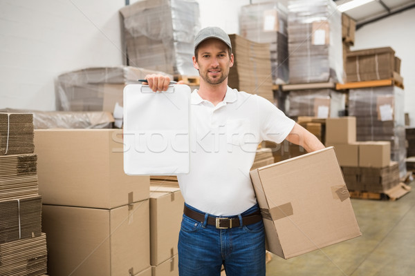 Delivery man with box and clipboard in warehouse Stock photo © wavebreak_media