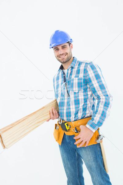 Happy construction worker holding wooden planks Stock photo © wavebreak_media