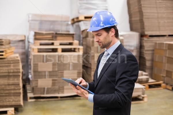 Warehouse manager wearing hard hat using tablet Stock photo © wavebreak_media