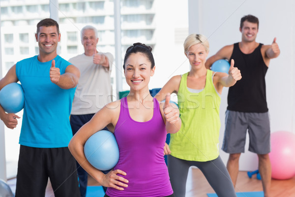 Instructor with class gesturing thumbs up at gym Stock photo © wavebreak_media