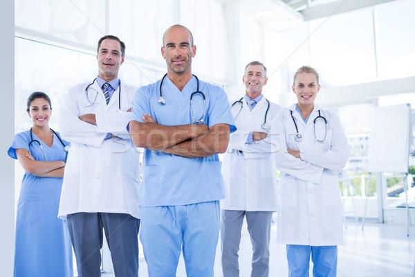 Equipo sonriendo médicos mirando cámara los brazos cruzados Foto stock © wavebreak_media