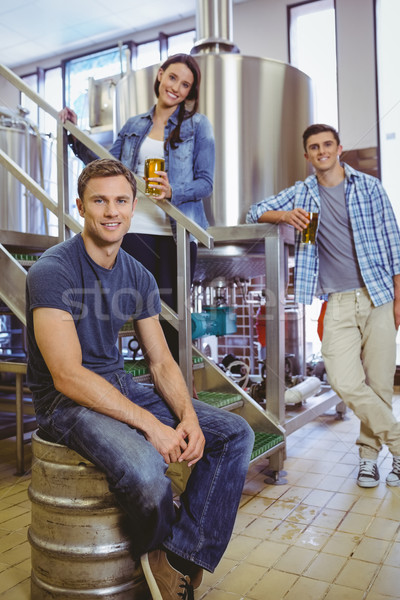 Man siting on keg and his colleague holding a glass of beer Stock photo © wavebreak_media