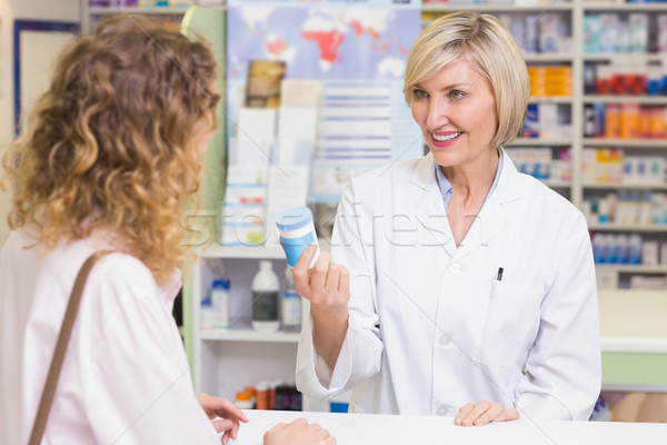 Pharmacist showing medicine jar to costumer  Stock photo © wavebreak_media