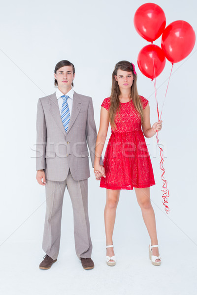 Unsmiling geeky couple standing hand in hand Stock photo © wavebreak_media
