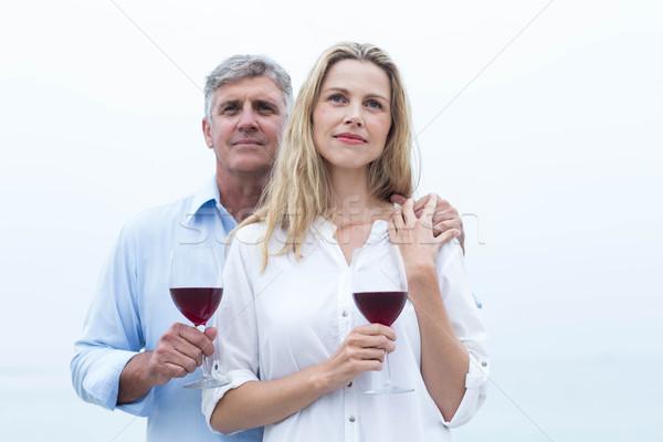 Happy couple holding a glass of red wine Stock photo © wavebreak_media