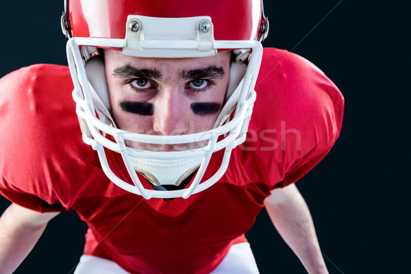 Portrait of a serious american football player taking his helmet Stock photo © wavebreak_media