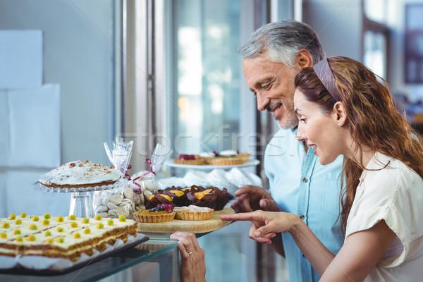 Happy couple pointing cakes Stock photo © wavebreak_media