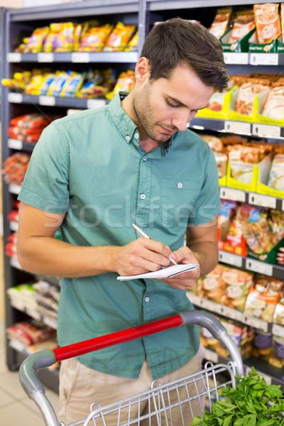 Ernstig man schrijven lijst notepad supermarkt Stockfoto © wavebreak_media