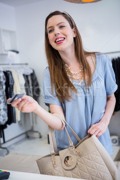 Brunette paying at till with credit card Stock photo © wavebreak_media