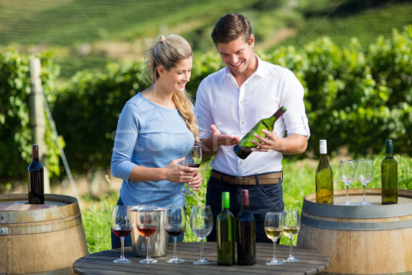 Happy man showing wine bottle to woman while standing by table Stock photo © wavebreak_media