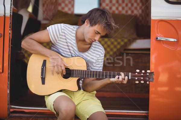 Fiatalember játszik gitár ül motor otthon Stock fotó © wavebreak_media