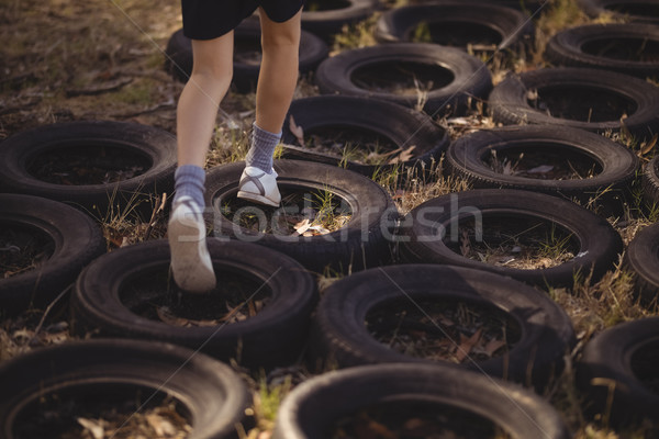Low section of girl running over tyres during obstacle course Stock photo © wavebreak_media