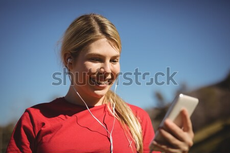 Encajar mujer escuchar música teléfono móvil Foto stock © wavebreak_media