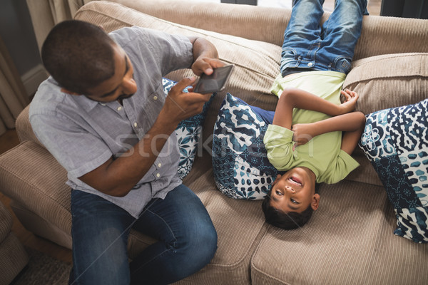 Man photographing his son lying on couch at home Stock photo © wavebreak_media