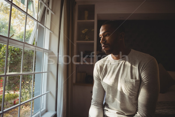 Thoughtful man sitting by window at home Stock photo © wavebreak_media