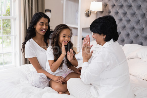 Happy multi-generation family playing patty cake on bed Stock photo © wavebreak_media
