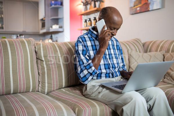 Homem falante telefone usando laptop sala de estar casa Foto stock © wavebreak_media