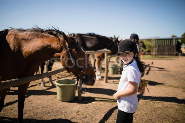 Smiling girl standing near the horse in ranch Stock photo © wavebreak_media