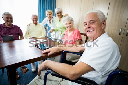 Portrait of smiling female doctor sitting with senior man and women on sofa Stock photo © wavebreak_media