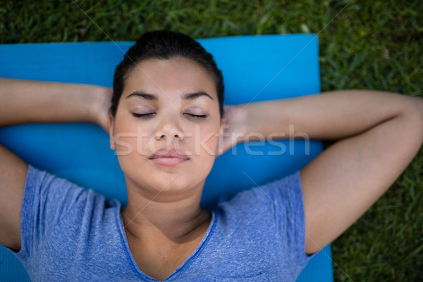 Trainer with closed eyes resting on exercise mat Stock photo © wavebreak_media