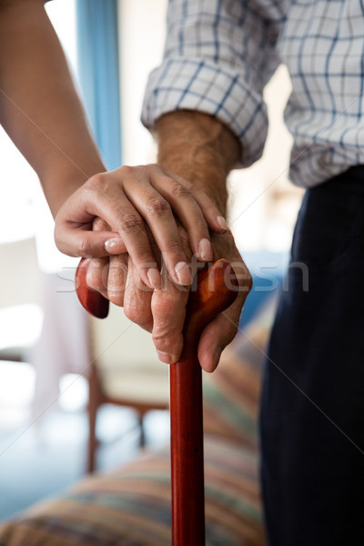 Hands of female doctor and senior man holding walking cane in retirement home Stock photo © wavebreak_media