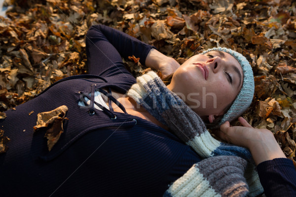 Close up of woman with hands behind head lying on dry leaves at park Stock photo © wavebreak_media